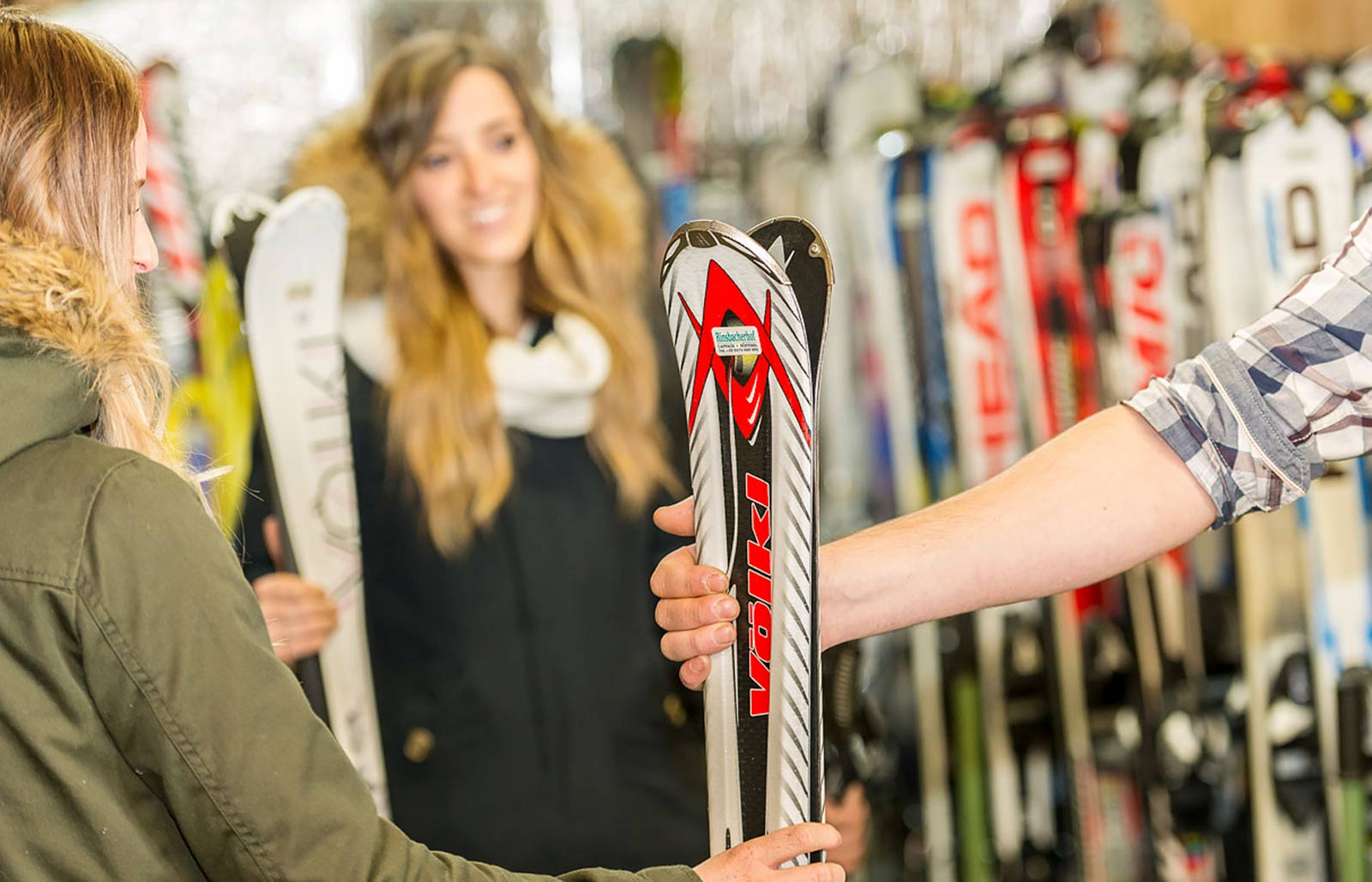 A girl rents some ski equipment in the ski rental in Rinsbacherhof.