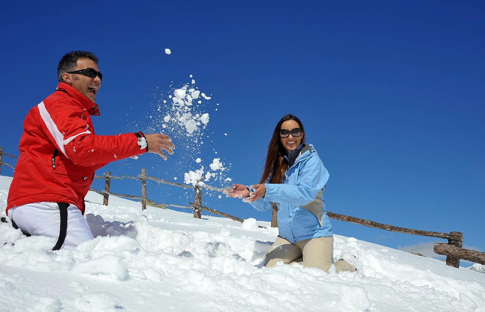 A couple is playing with snow in the South Tyrolean Dolomites