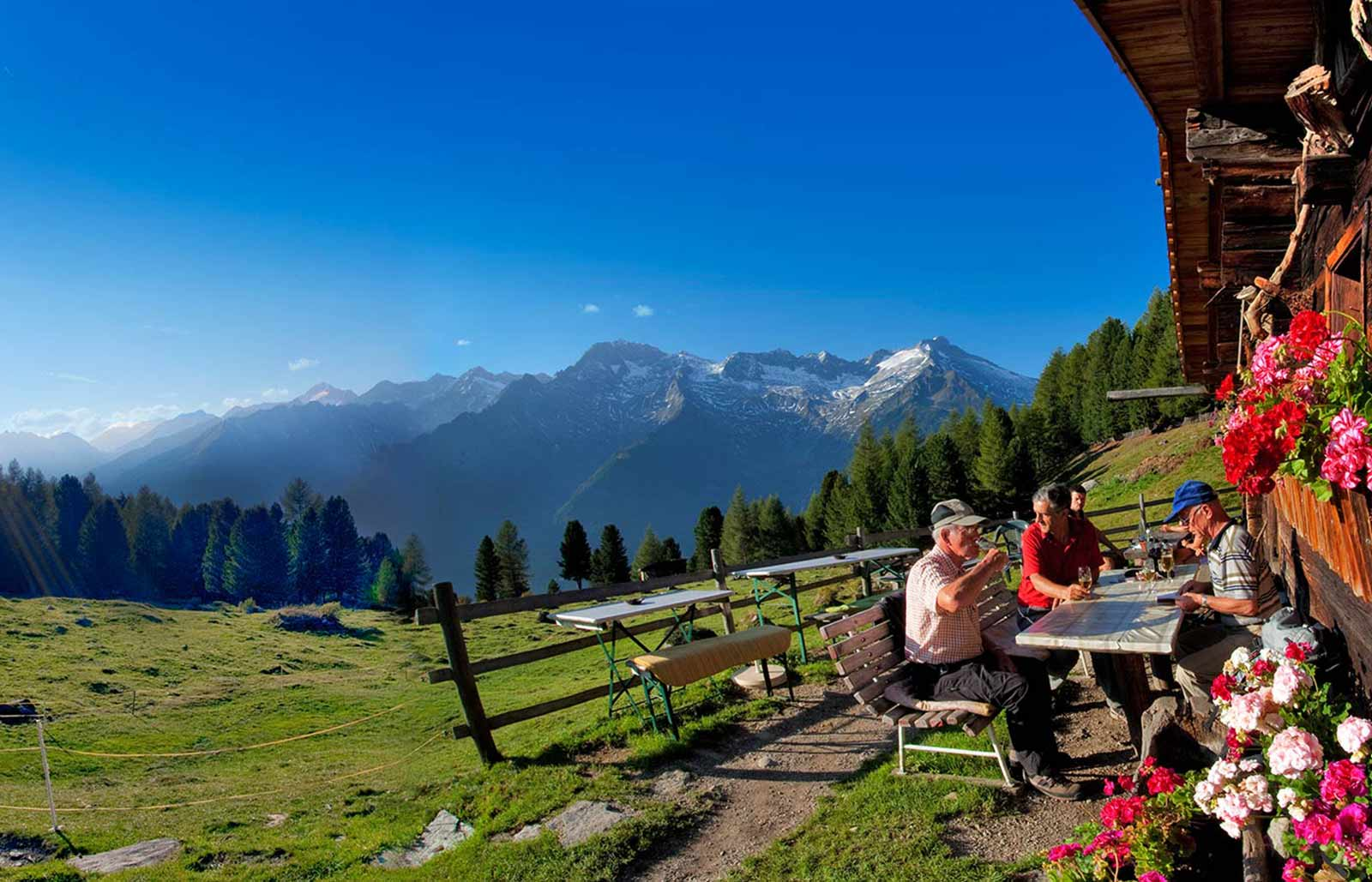 A hiking group is taking a break, drinking a beer in the Southtyrolean Dolomites