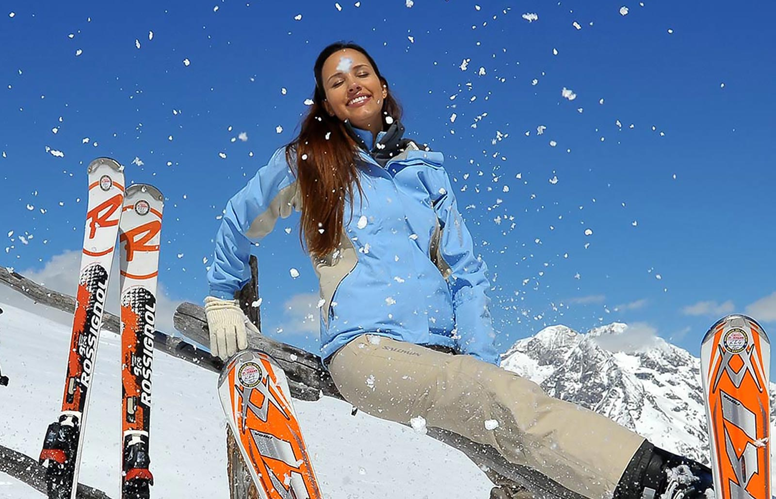 A young lady enjoys the sun on the piste with her skis