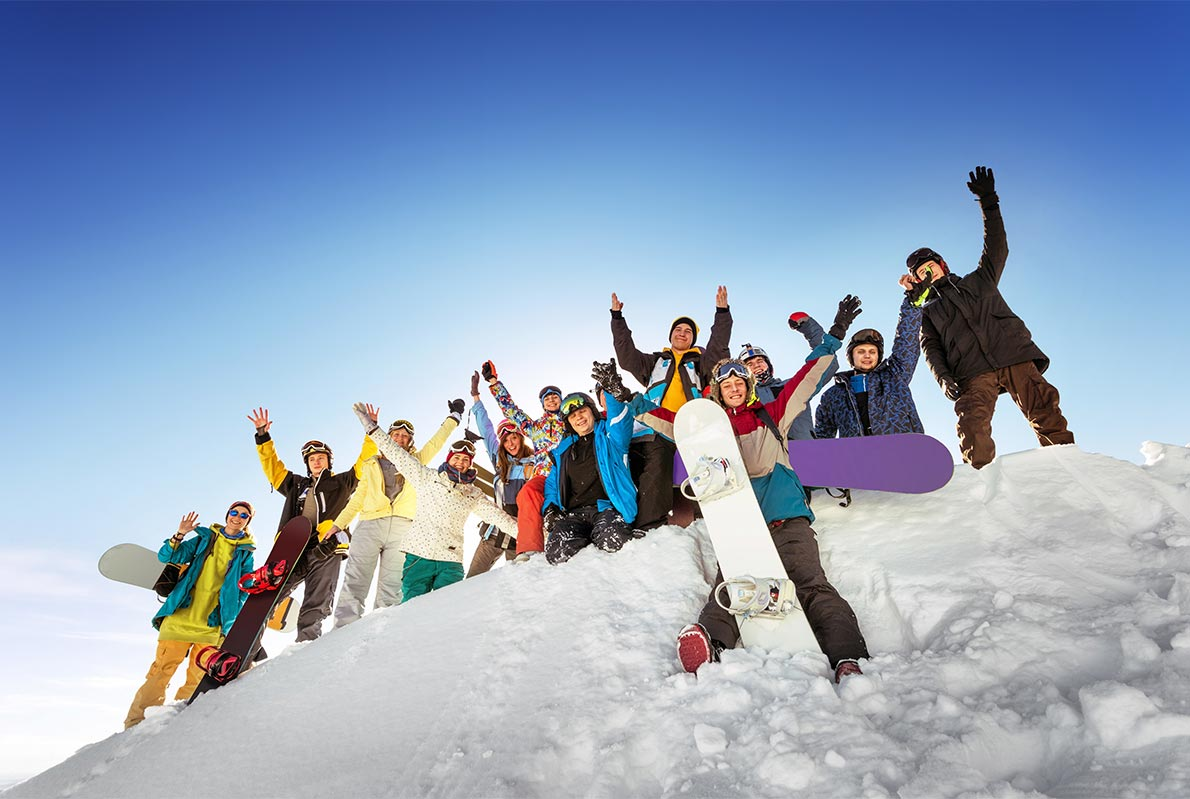 Group of teenagers with snowboards on a snowy hill