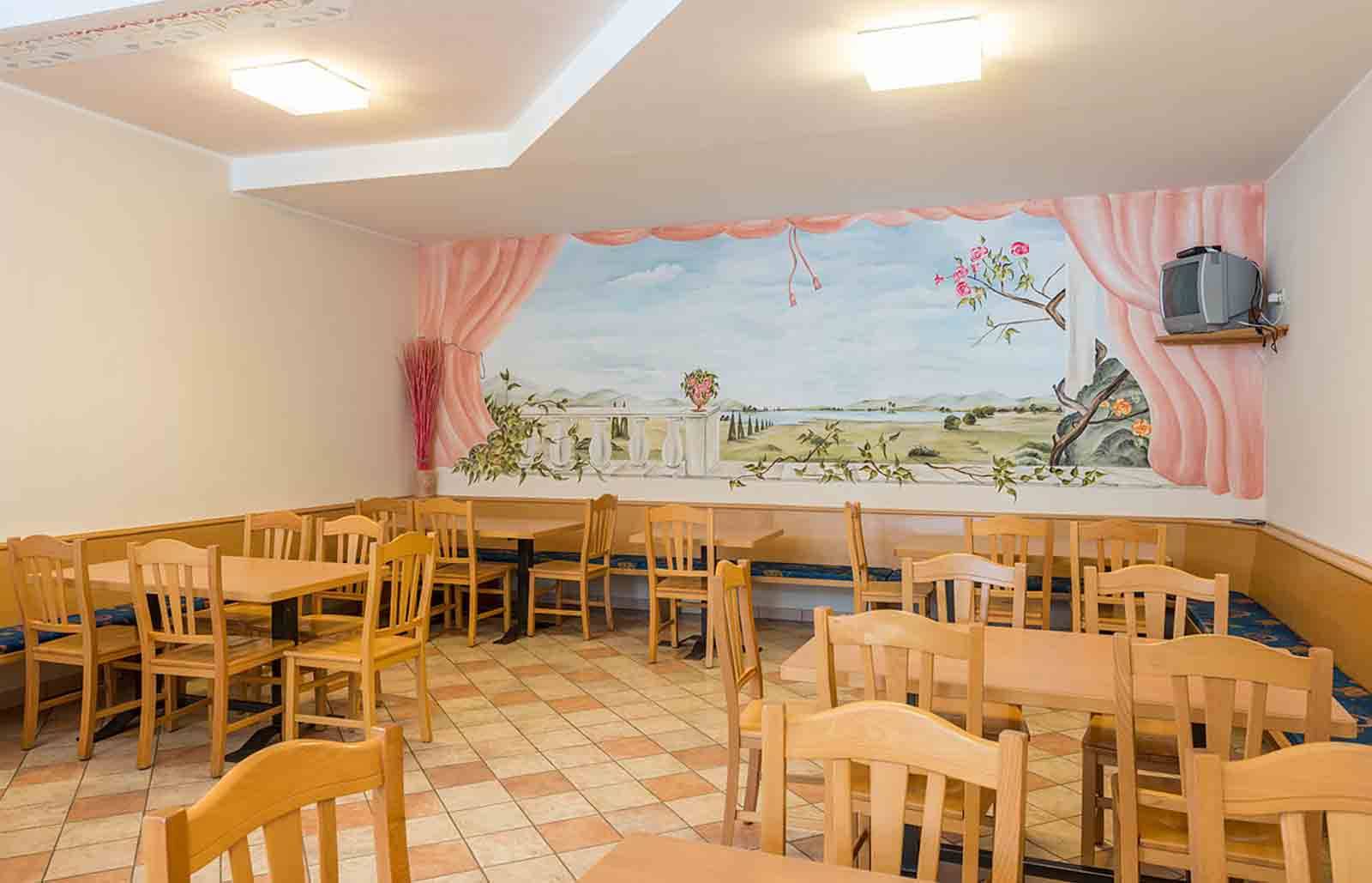The dining room at Rinsbacherhof has wooden furnishing, on the wall there is a big painting of a landscape on the wall